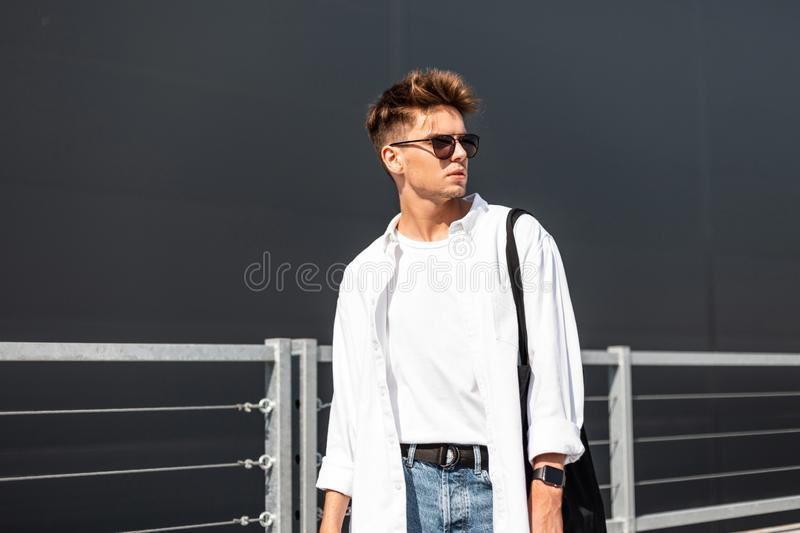 Fashionable young hipster man in stylish white clothes in blue jeans in trendy sunglasses in a black vintage bag is standing. Near a modern building in the city royalty free stock photo