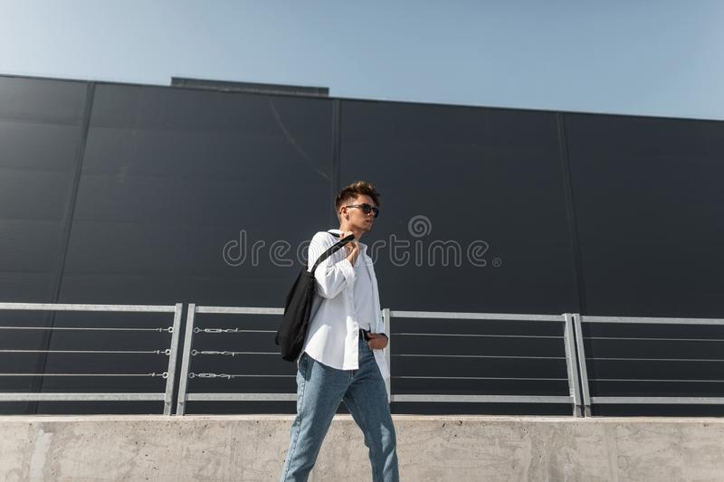 Fashionable young hipster man in trendy white clothes in sunglasses with a stylish hairstyle with a black bag walks on the city. On a sunny day. American guy royalty free stock photos
