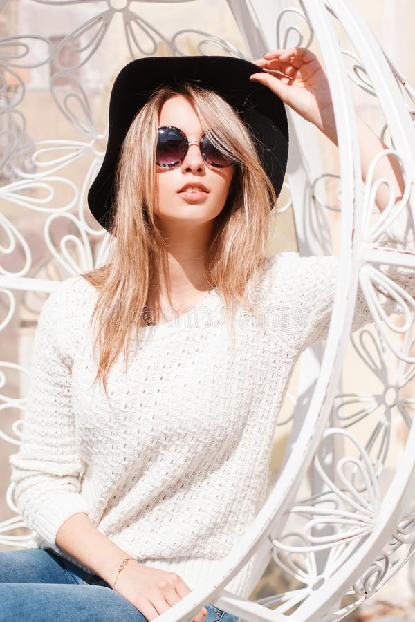 Fashionable young hipster woman in a luxurious black hat in blue jeans in sunglasses in a knitted sweater is sitting outdoors. In a vintage metal white chair on royalty free stock image