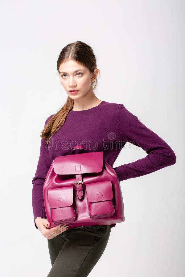 A fashionable young lady in sweater and jeans, a violet pink leather bagpack on her hand. stock photo