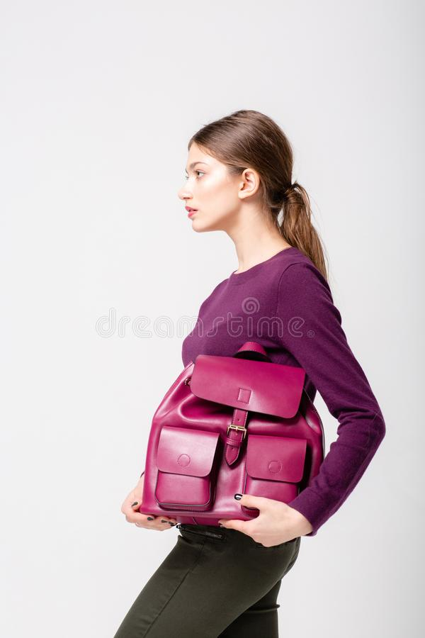 A fashionable young lady in sweater and jeans, a violet pink leather bagpack on her hand. royalty free stock photos