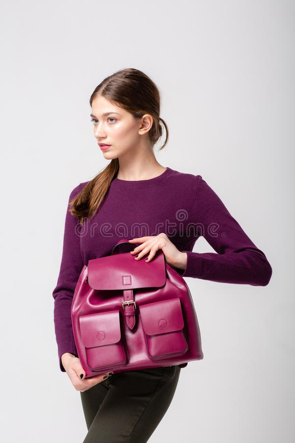 A fashionable young lady in sweater and jeans, a violet pink leather bagpack on her hand. stock photography