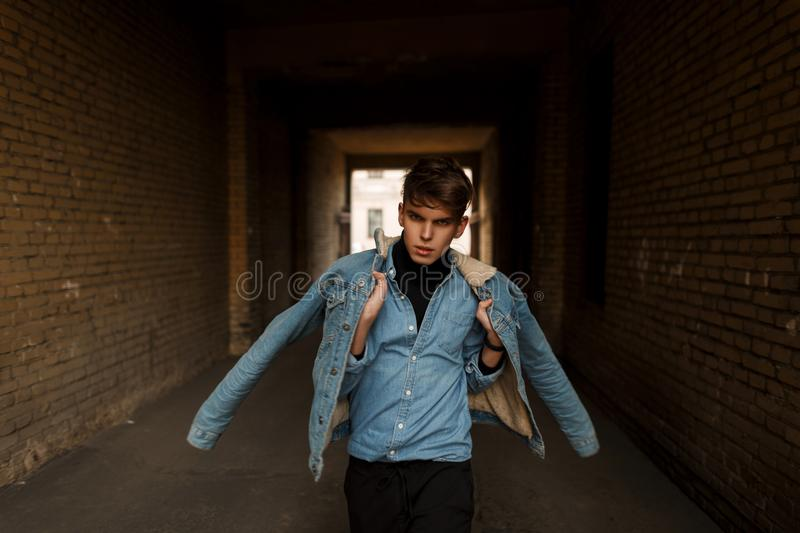 Fashionable young male model in stylish denim clothes posing stock photos