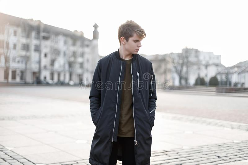 Fashionable young man with a hairstyle in a stylish autumn black jacket in a t-shirt in black stylish jeans walks around the city. American cool guy stock photos