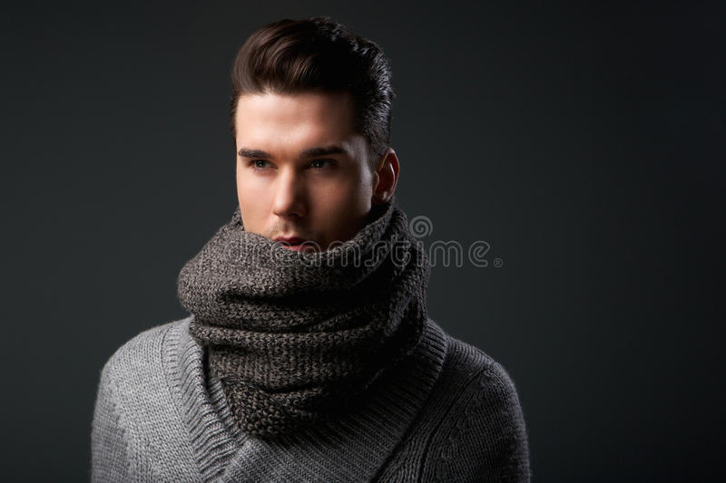 Fashionable young man posing with gray wool scarf. Close up portrait of a fashionable young man posing with gray wool scarf stock photo