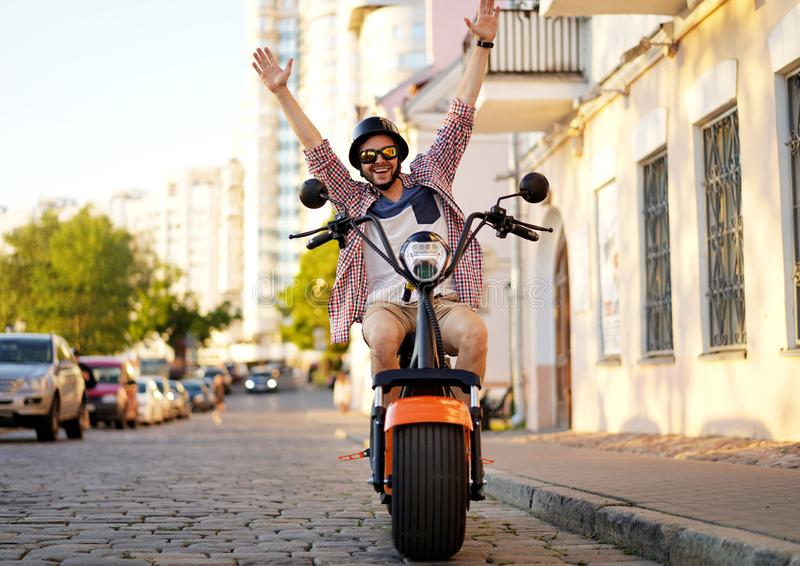 Fashionable young man riding a orange motorbike in the street. stock images