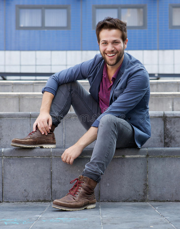 Fashionable young man smiling outdoors royalty free stock image