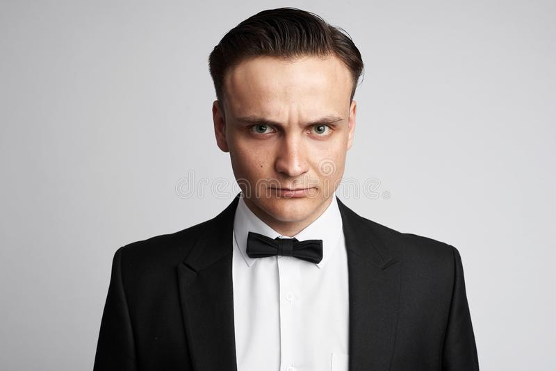 Fashionable young man wearing suit and bow tie. Angry guy isolated. Fashionable young man wearing suit and bow tie. Angry guy studio shot stock image