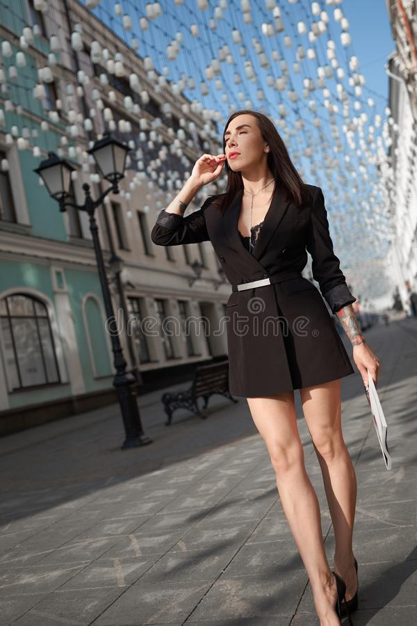 Fashionable young model in design clothes. Wall king on the street royalty free stock photography