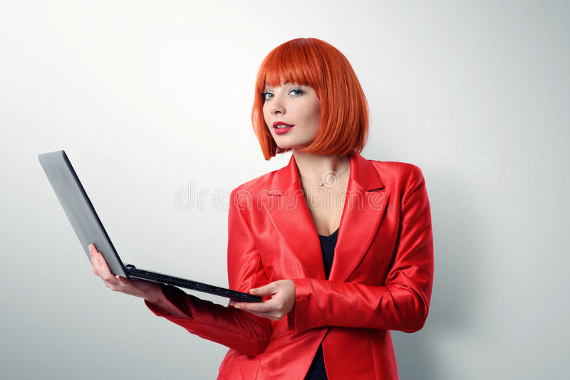 Fashionable young redhead woman in red holding a laptop. On background stock images