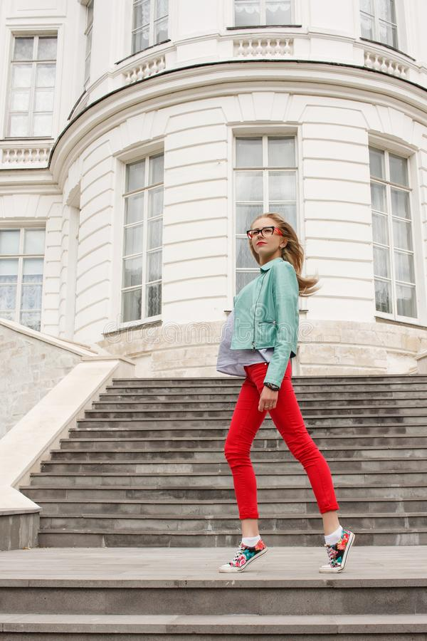 Fashionable young slim blonde girl posing on the stairs. Stylish woman`s look. royalty free stock image