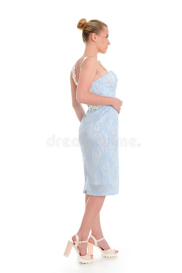 Fashionable young woman in beautiful blue dress posing at studio royalty free stock images