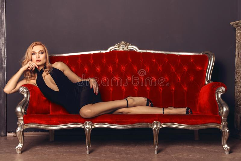 Fashionable young woman in a black evening dress lies on a red antique couch royalty free stock image