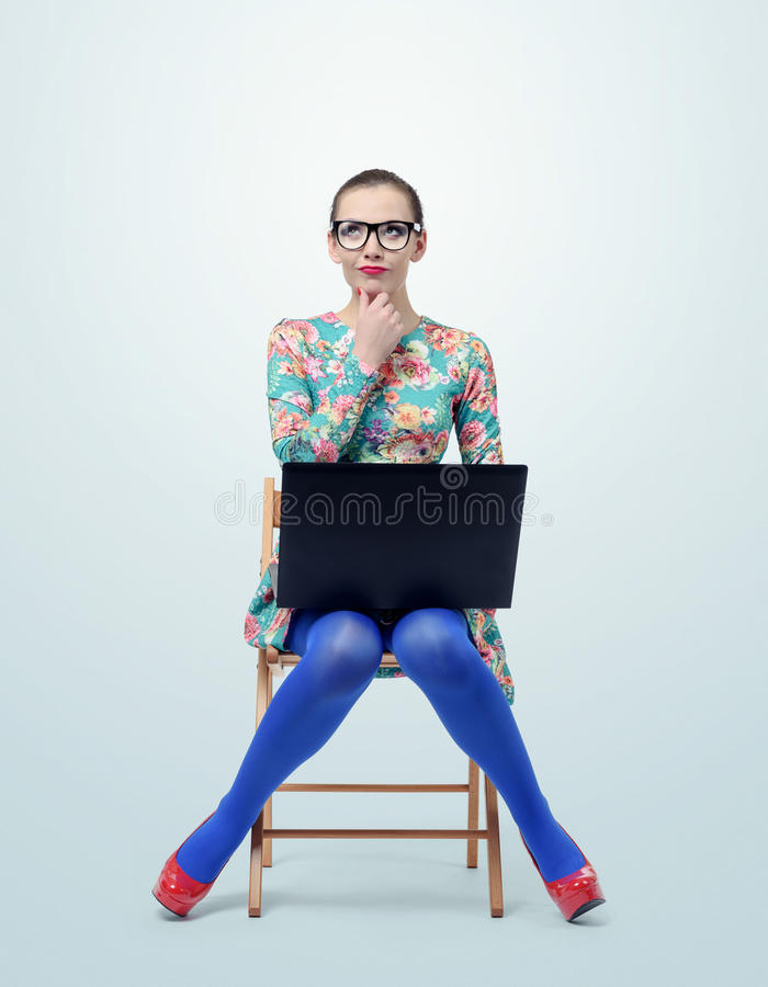 Fashionable young woman in dress and glasses sitting on chair with a laptop stock photography