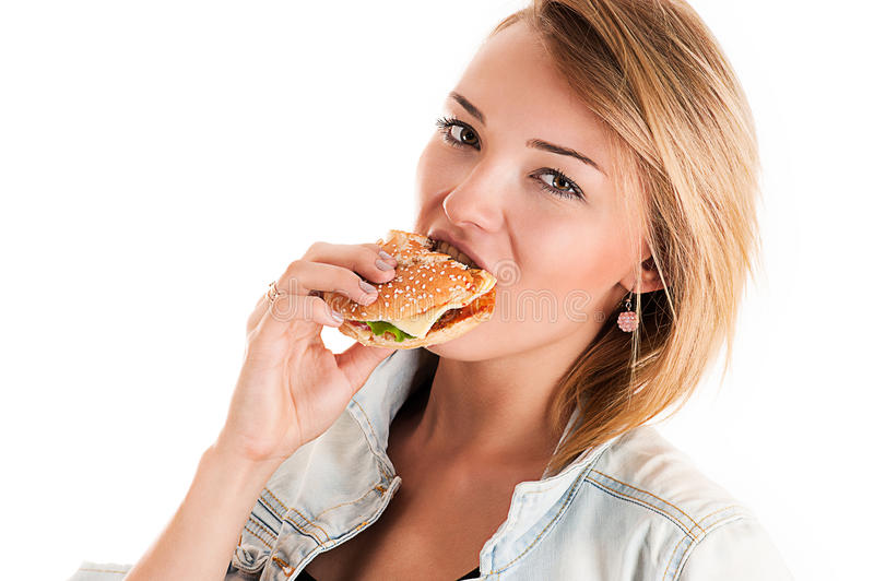 Fashionable young woman eating a hamburger. Isolated on white stock photos