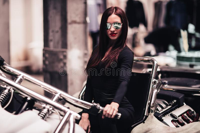 Fashionable young woman in mirrored glasses, posing on a custom motorcycle. Photo with copy space royalty free stock photo