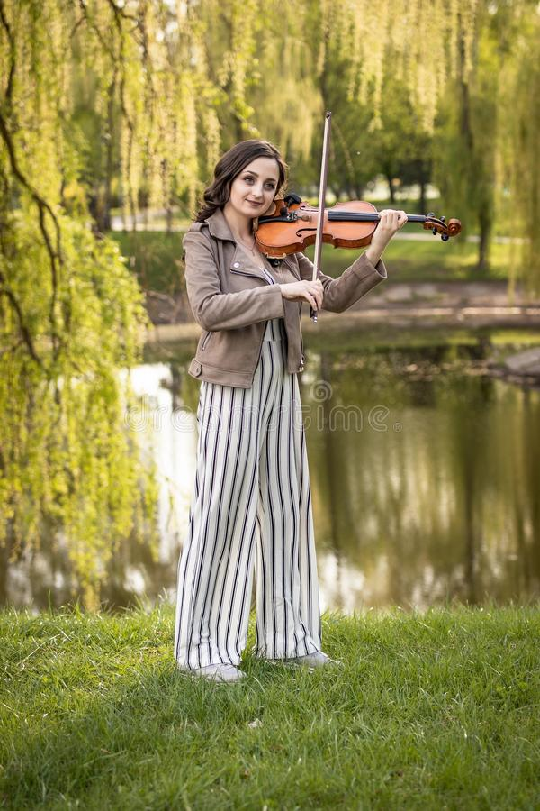 Fashionable young woman playing the violin in the park. The general plan stock image