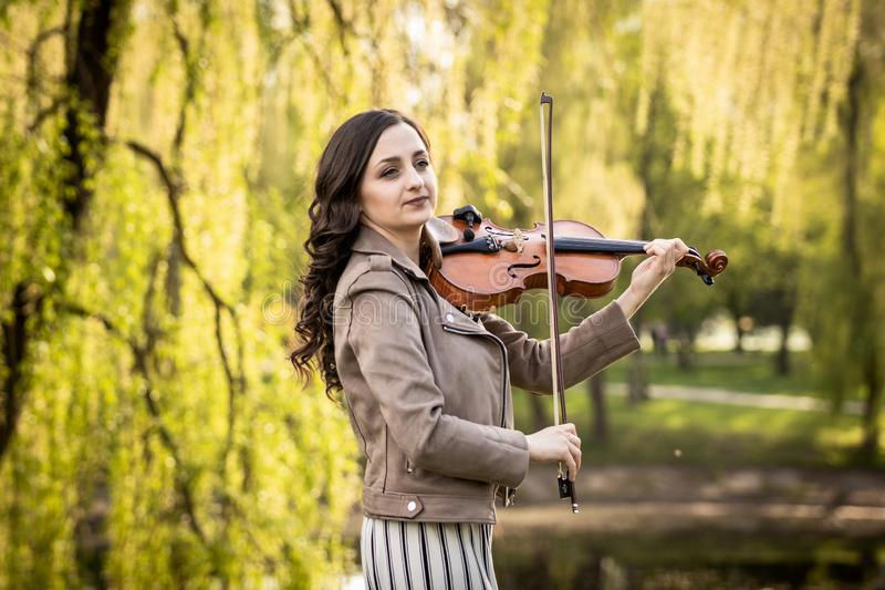 Fashionable young woman playing the violin in the park. The half-size portrait royalty free stock image