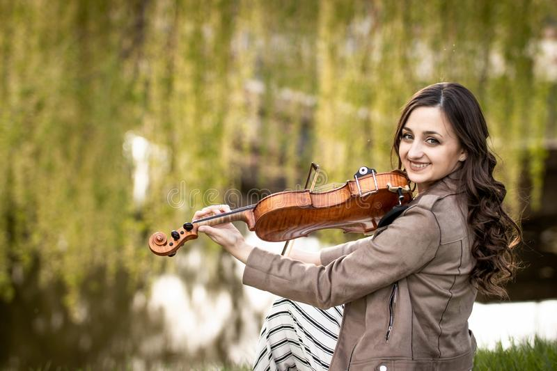 Fashionable young woman playing the violin in the park and smiles stock image