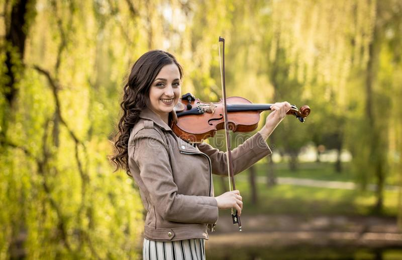 Fashionable young woman playing the violin in the park and smiles. The half-size portrait royalty free stock photos