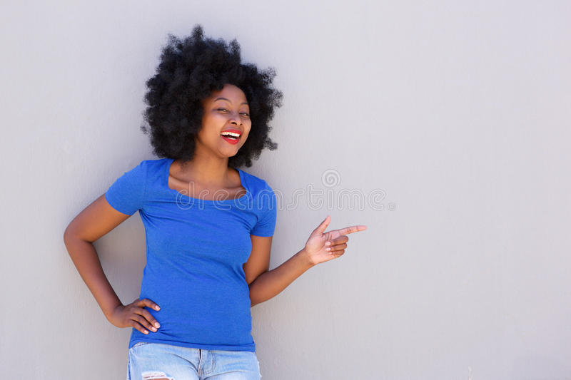 Fashionable young woman smiling and pointing to wall stock photography