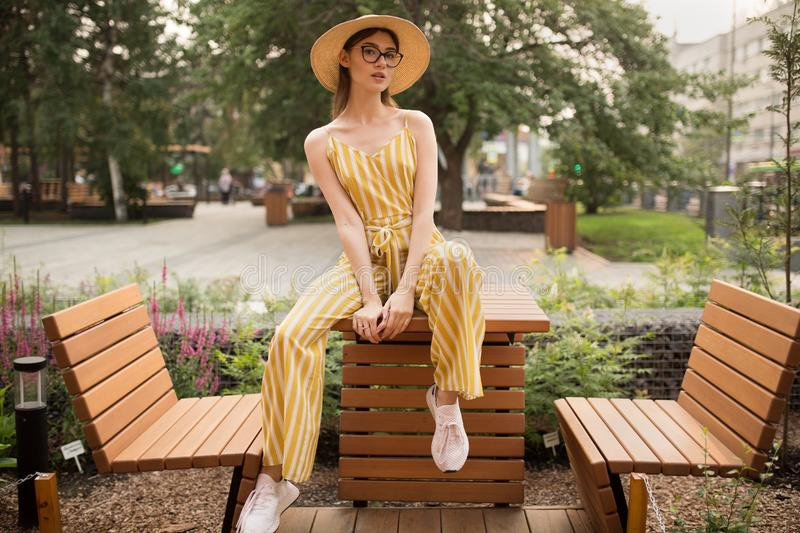 Fashionable young woman in stylish clothes. Sitting pose. Open fresh air. City stock photography
