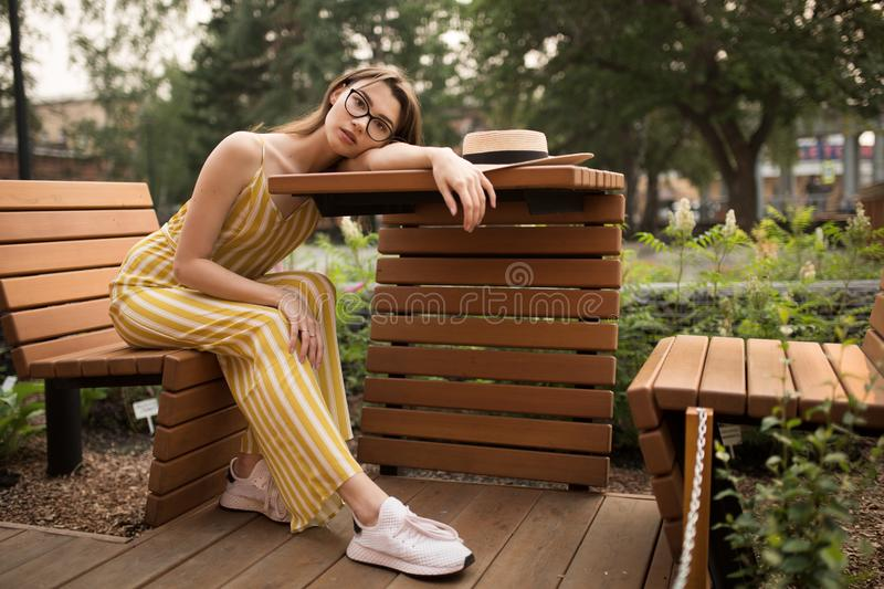 Fashionable young woman in stylish clothes. Sitting pose. Open fresh air. City stock image