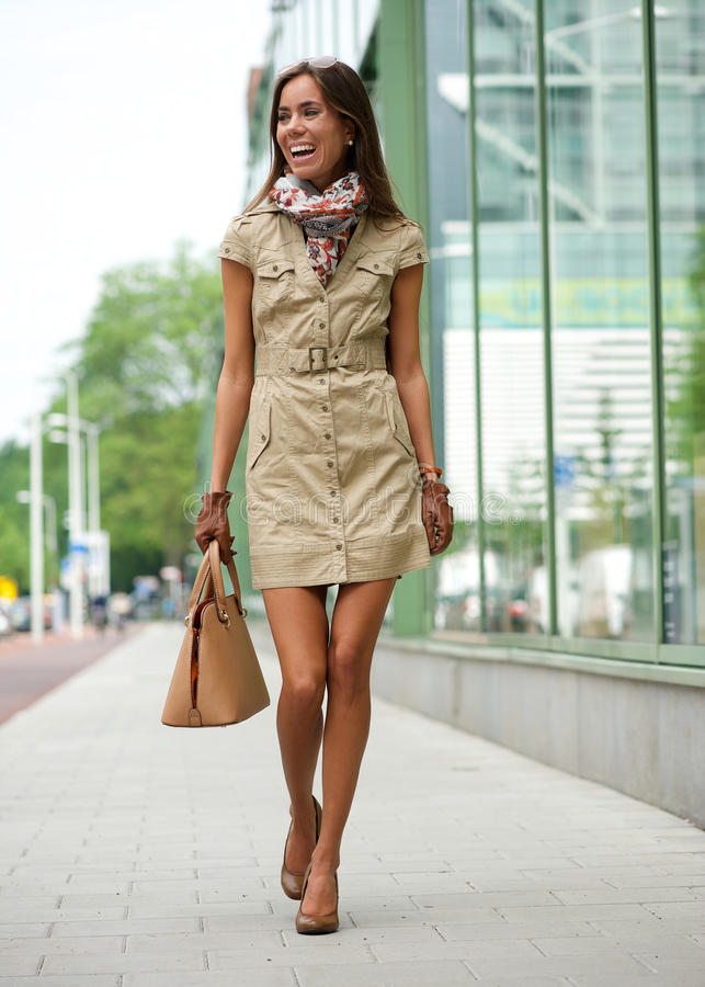 Fashionable young woman walking in the city royalty free stock photos