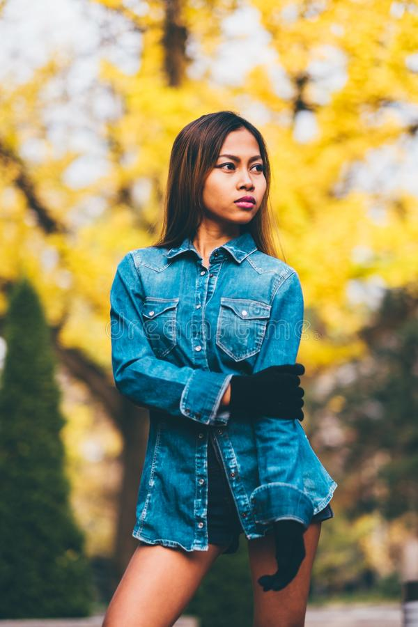 Fashionable young woman wearing blue jeans jacket with the high hills and long stripe knee socks. autumn fashion style.  stock image