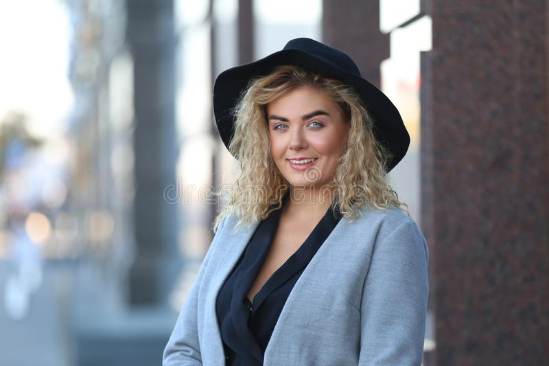 Fashionable young woman wearing hat outdoors royalty free stock images