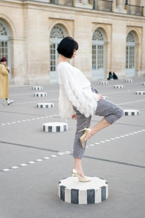 Fashionable young woman in white blouse and high heel shoes on city streets. Fashion in Paris, France.  royalty free stock photo
