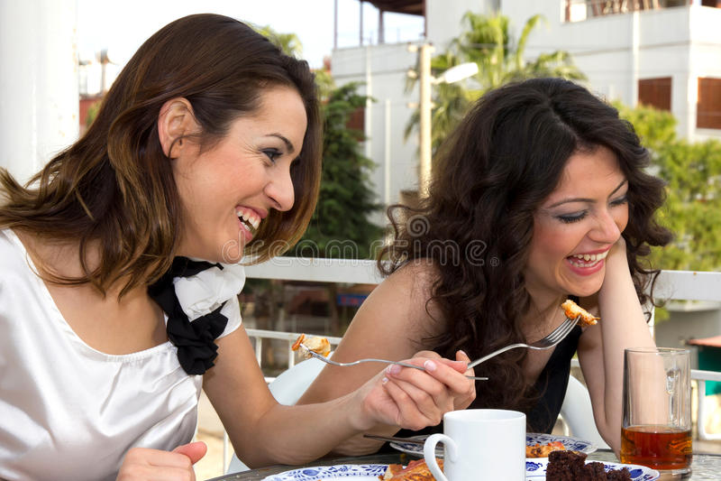 Fashionable Young Women. Laughing and koking at a restaurant over a morsel of food that is being offered over the table on a fork royalty free stock image