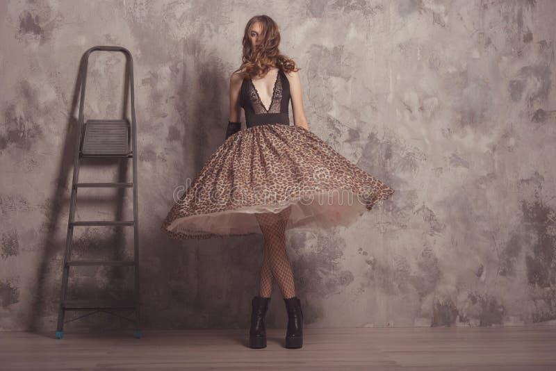 Fashionable zelfverzekerde vrouw in lichaamskleding met luipaard print, vrouwelijk model in studio met betonnen achtergrond Vintk stock foto