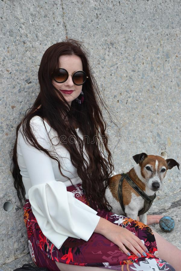 A brunette young caucasian lady sitting with her Jack Russell terrier dog royalty free stock image