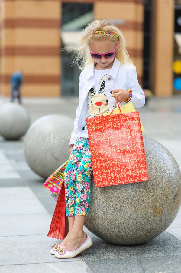 Fashionably dressed little girl with shopping bags royalty free stock images