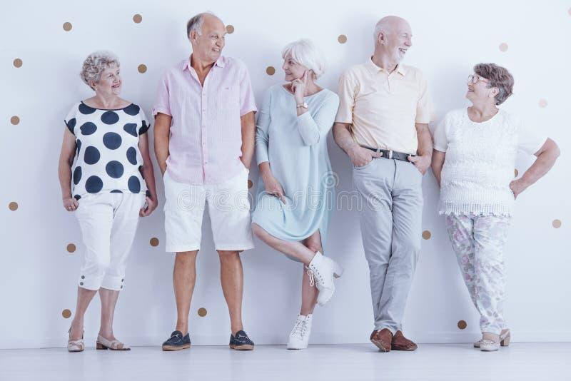 Fashionably dressed smiling senior people posing in bright studio stock photo