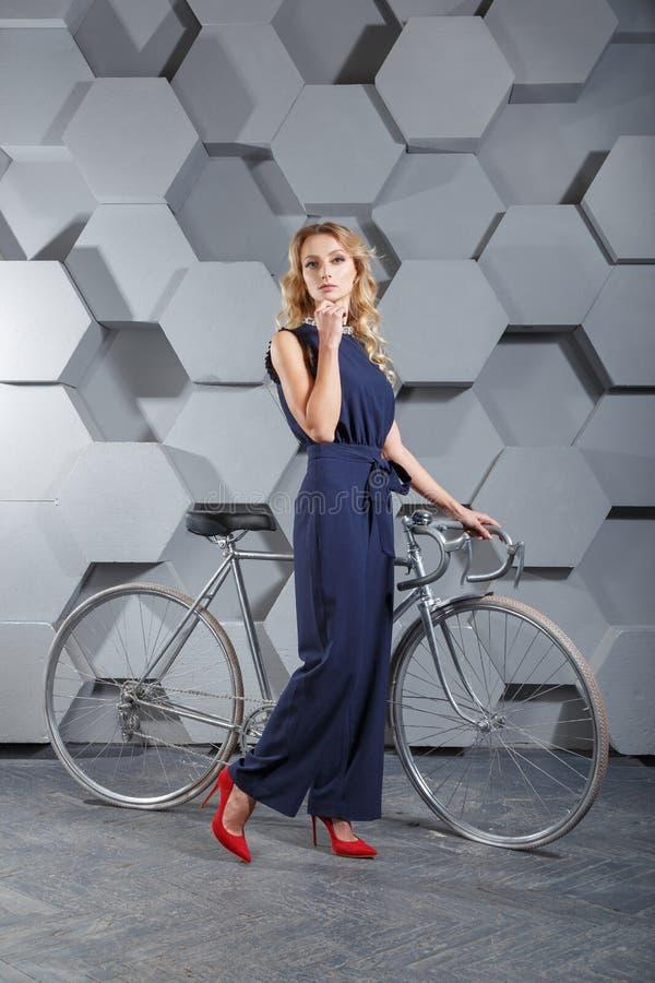 Fashionably klädd ung blond kvinna i sommar som poserar överallt med den röda retro cykeln för tappning arkivbilder