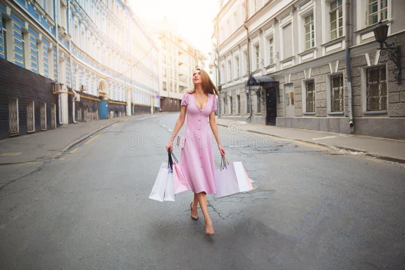 Fashionably kleedde vrouw op de straten van een kleine stad, het winkelen concept stock foto's