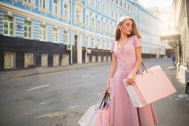 Fashionably påkläddkvinna på gatorna av en liten stad som shoppar begrepp royaltyfria bilder