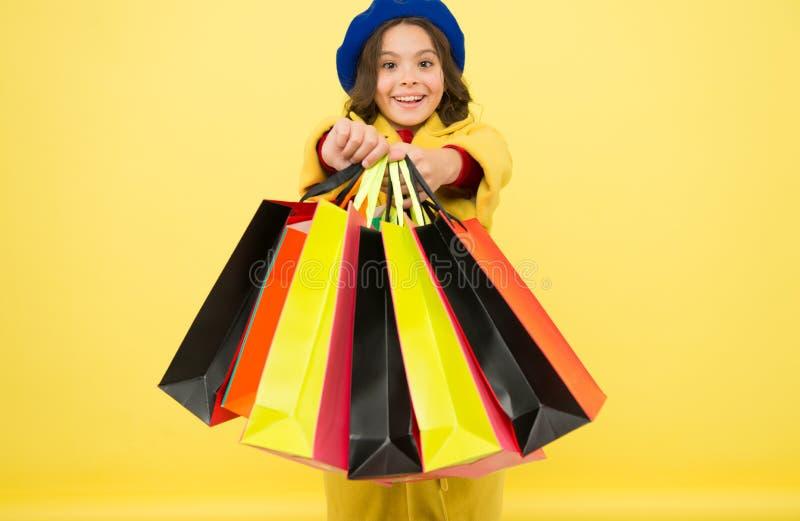Fashionista崇拜购物 被购物占据心思 在黄色背景的女孩逗人喜爱的孩子举行购物带来 中间季节 库存图片