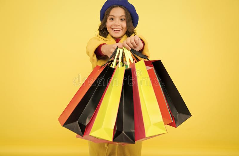 Fashionista adore shopping. Obsessed with shopping. Girl cute kid hold shopping bags on yellow background. Mid season royalty free stock image