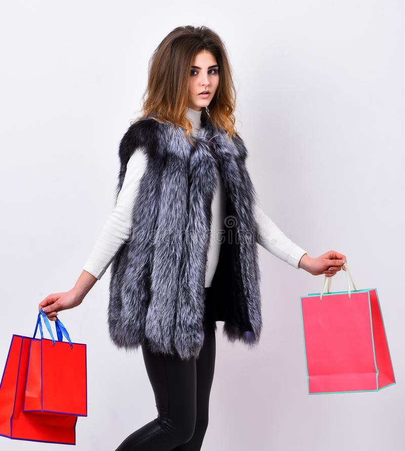 Fashionista buy clothes in shop. Girl makeup face wear fur vest white background. Woman shopping luxury boutique. Lady stock image
