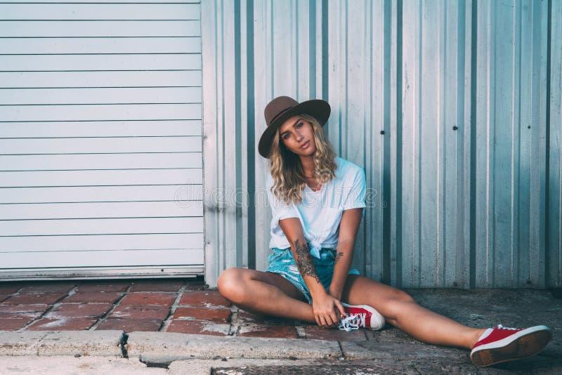 Fashionista dziewczyny obsiadanie w backstreet zdjęcia royalty free