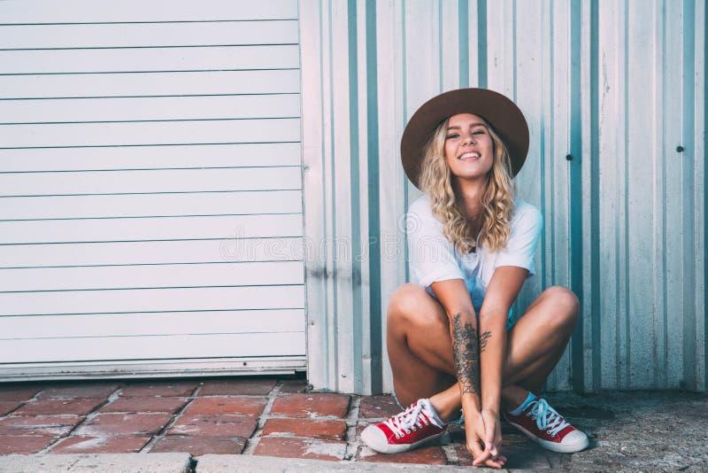 Fashionista dziewczyny obsiadanie w backstreet zdjęcia stock