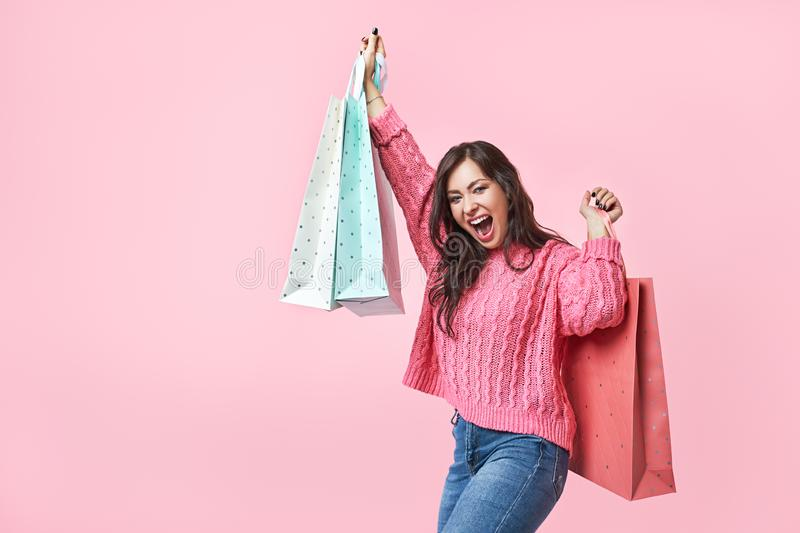 Fashionista girl with bags. Young brunette woman with purchases. Joyful beauty was on sale, on a pink background royalty free stock images