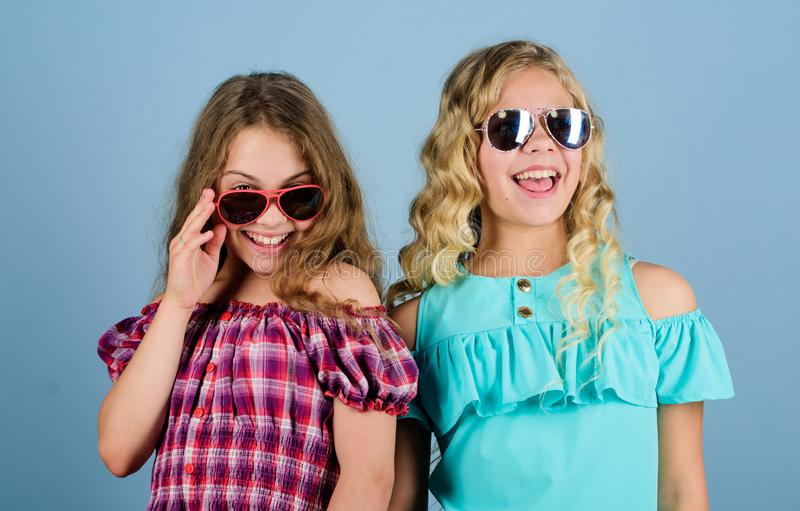 Fashionista. kid summer fashion. hairdresser salon. beauty and fashion. long blond curly hair. cheerful small girls in. Sunglasses. trendy sisters. friendship stock photography