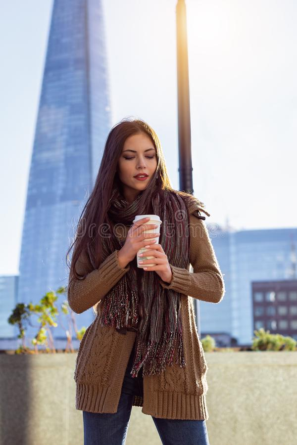 Fashionista woman in outdoors London, UK. Attractive urban fashionista woman with a coffee in her hand in outdoors London, UK royalty free stock photo