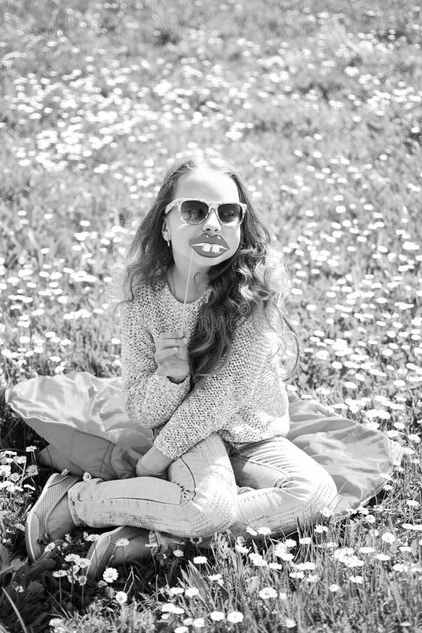 Fashionistaconcept Kind het stellen met zonnebrilkarton het glimlachen lippen voor fotozitting bij weide Meisje op vrolijk stock afbeeldingen