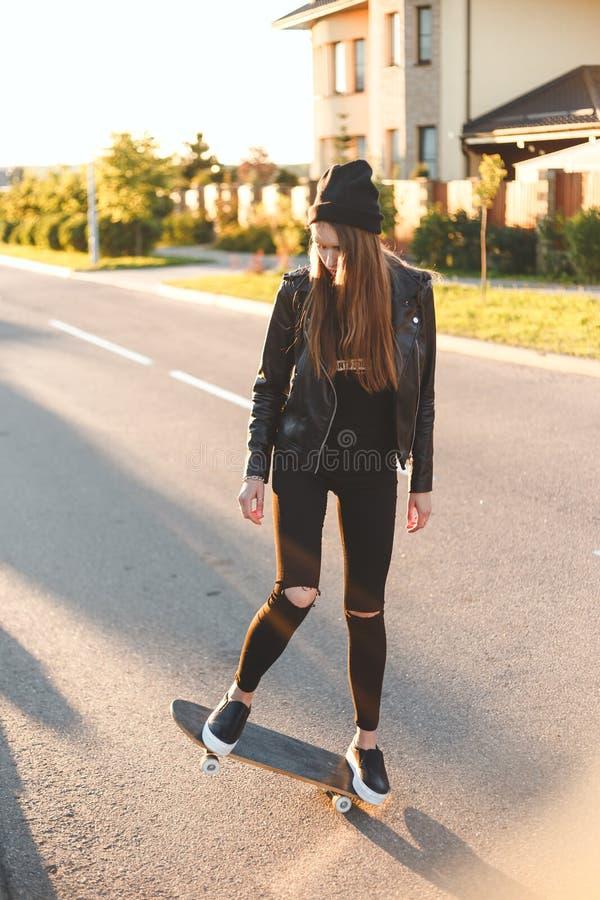 Fashionly a habillé la fille patinant sur la planche à roulettes, dehors image libre de droits