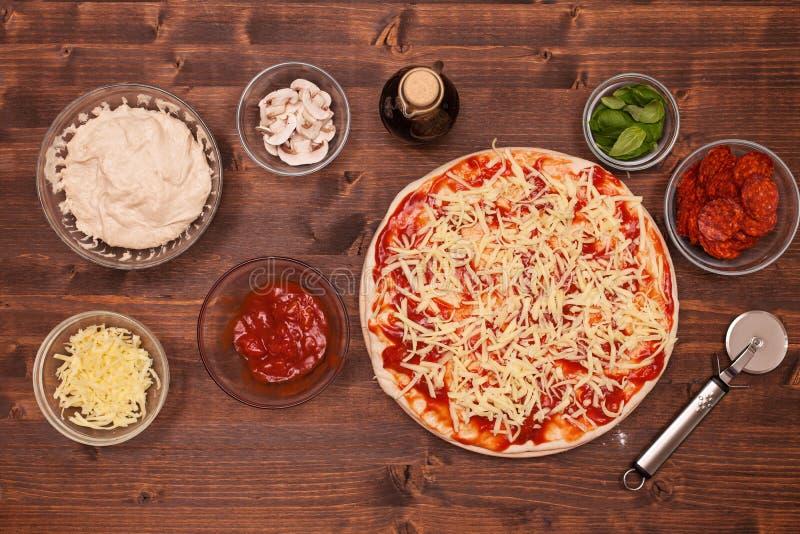 Fasi di produrre una pizza - mettendo sul formaggio grattugiato fotografia stock libera da diritti